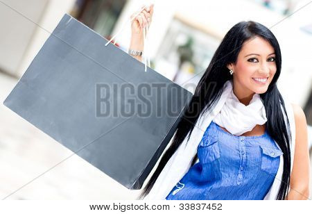 Beautiful woman holding a shopping bag and smiling