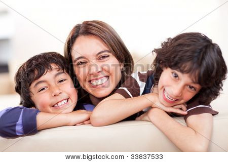 Happy mother with her two sons smiling at home