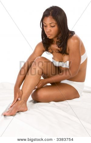 Beautiful Black Girl Applies Moisturizer On Legs