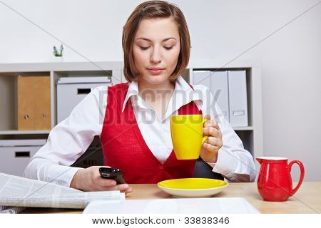 Woman in office taking a break with cup of coffee and smartphone