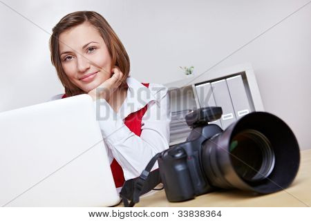 Happy female photographer in studio with camera and laptop computer
