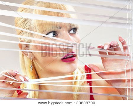 Beautiful scared woman is looking through jalousie