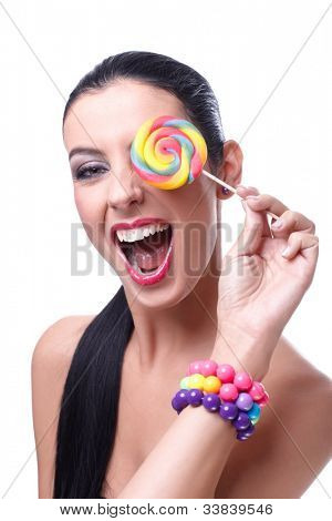 Attractive wild woman laughing, holding colorful lollipop over left eye.