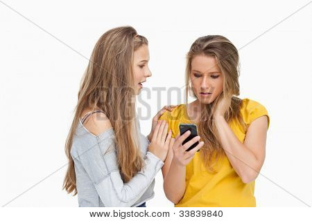 Upset young woman holding her cellphone consoled by her friend against white background