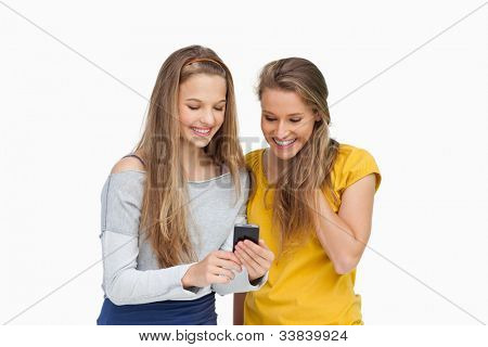 Two smiling students looking a cellphone screen against white background