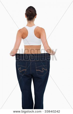 Rear view of a woman who lost a lot of weight against white background