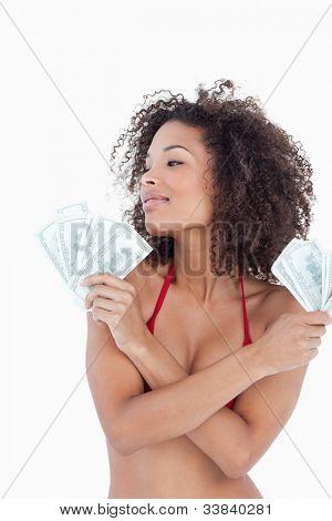 Junge attraktive Frau Wegsehen halten zwei Fans von Banknoten