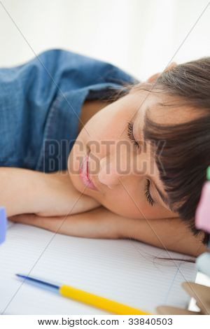 Close-up of a female student sleeping among her books on her desk