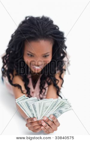 A young excited woman holding American dollars in her hands is smiling against a white background