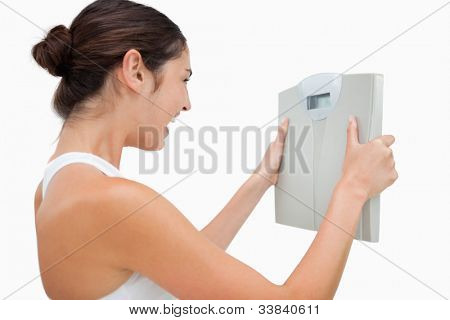 Young woman happy while holding a scales against white background