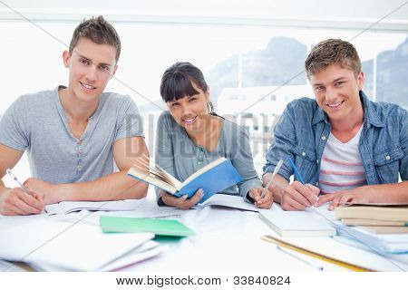 Three smiling students doing homework together as they all look into the camera