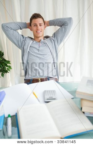 Student stretching while smiling in front of his homework