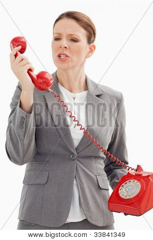 An angry businesswoman is shouting at the phone