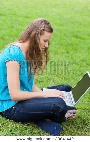 Young serious girl sitting cross-legged in the countryside while typing on her laptop