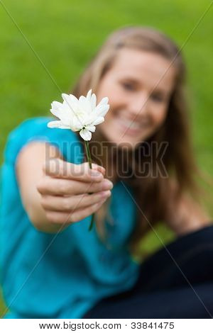 Beautiful white flower held by a smiling young girl in a park