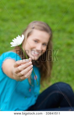 Beautiful white flower held by a young attractive girl sitting in the countryside