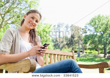 Smiling young woman writing a text message on a park bench