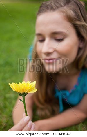 Beautiful yellow flower held by an attractive young girl