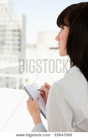 A business woman looks upwards as she stops writing on the notepad in her hand