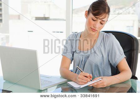 eine geschäftsfrau an ihrem Schreibtisch nimmt sich auf ihrem Merkzettel