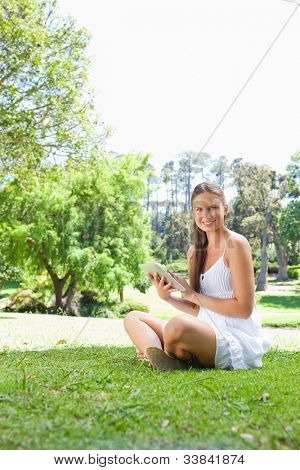 Smiling young woman on the grass with her tablet computer
