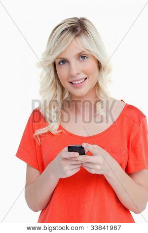 Woman beaming while sending a text with her cellphone against a white background