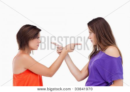 Two teenagers blaming each other while pointing their fingers