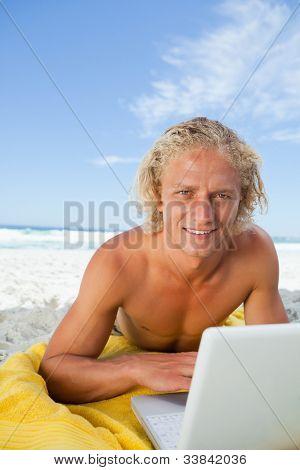 Hombre rubio sonriente mirando a la cámara mientras se está acostado detrás de su computadora portátil