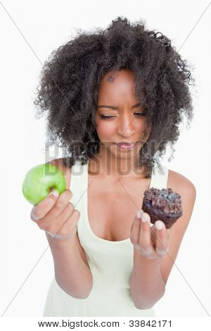 Young woman hesitating between a muffin and an apple against a white background