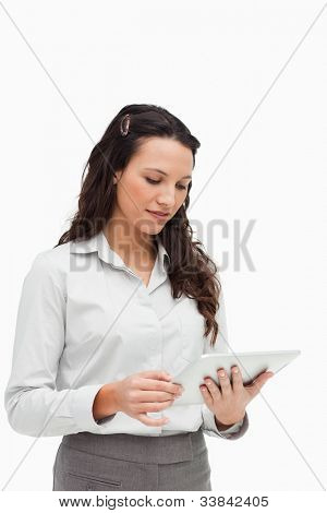 Brunette standing while using a touchpad against white background