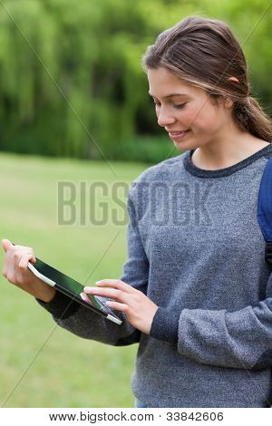 Young happy woman smiling while touching her tablet pc and standing in a park