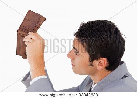 Mann in einem Anzug suchen in seine leere Brieftasche vor weißem Hintergrund