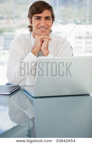 A smiling young businessman is resting his head on his hands
