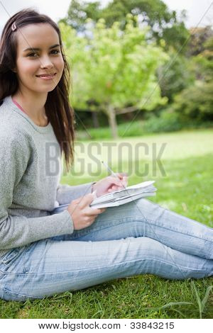 Young happy student sitting in a public garden while doing her homework