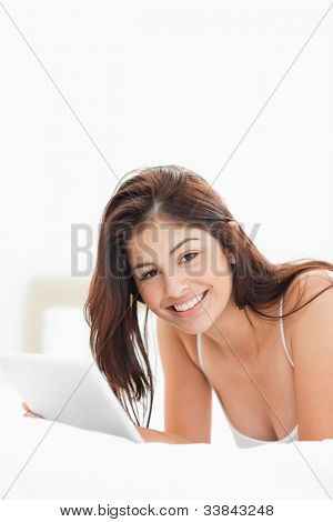 A woman lying on a bed while smiling and looking straight ahead, while using a tablet.