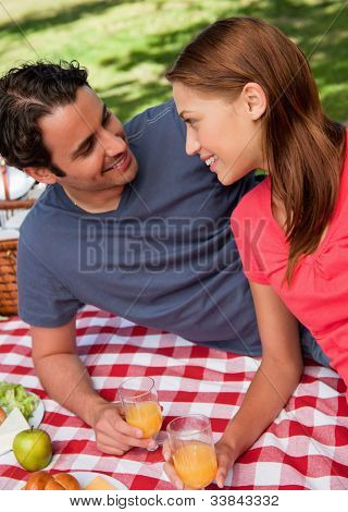 Close-up of two smiling friends looking into each others eyes while they hold glasses as they lie on a blanket with a picnic