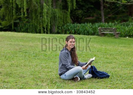 Smiling young adult reading a book while sitting cross-legged on the grass in a park