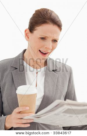 A surprised businesswoman is reading the newspaper