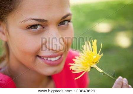 Woman looking towards the camera while holding a yellow flower with grass in the background