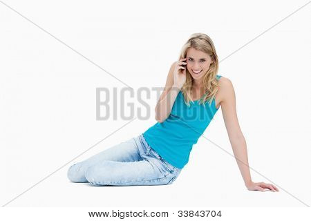 A smiling woman is sitting on the floor talking on her mobile phone against a white background