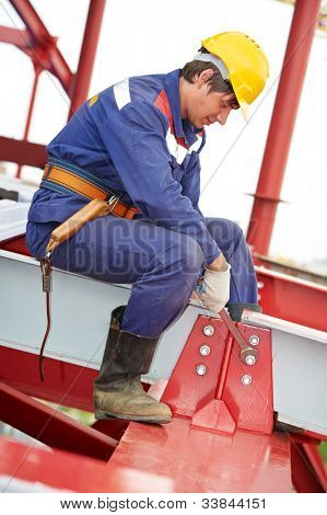 builder worker in uniform and safety protective equipment at metal construction frames installation and assemblage