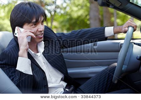 Man in a striped suit sits on a driver seat in a open top car and talk on a cell phone
