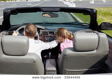Boy sits on driver seat in open top car and his sister sits on passenger seat, both unfastened with seatbelt, back view.