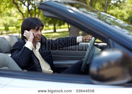 Man in a striped suit sits on a driver seat in a cabriolet and talk on a cell phone