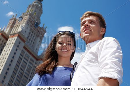 Young smiling couple stands on the background of blue sky near to Lomonosov Moscow State University .