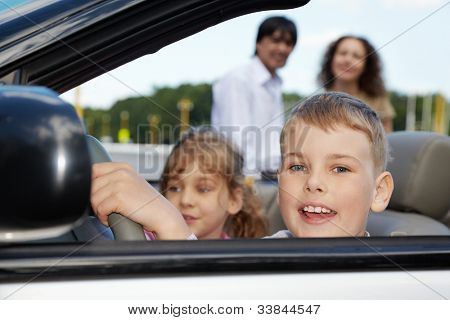 Close-up face of boy sitting at steering wheel of cabriolet, his sister and parents on background not in focus