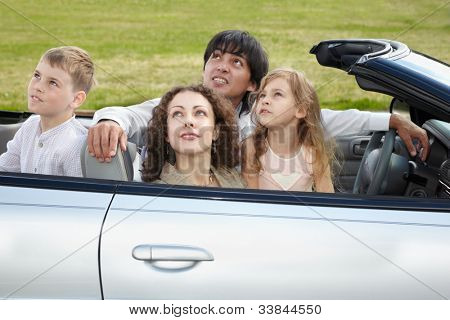 Family of four - parents and two children -  sits in cabriolet and looks on the sky.