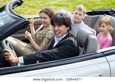 Familia de cuatro miembros se sienta en el coche superior abierto, enfocado al conductor en el traje de rayados