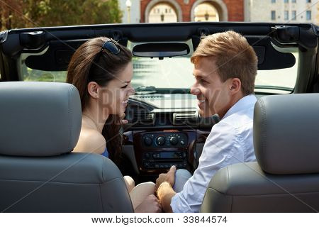 Young smiling girl and a guy sit in the car, standing against building with two arches, and look at each other, back view