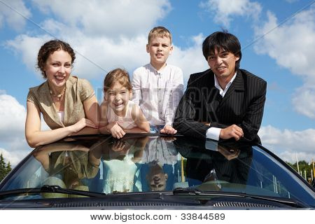A family of four - parents and two children - stands in a cabriolet on front seats, leaning on the windshield, background is blue sky with  white clouds